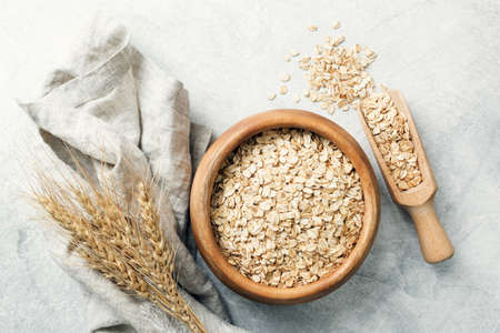 Rolled oats in wooden bowl and ears of wheat on grey background. Table top view. Healthy eating, healthy lifestyle, gluten free diet concept