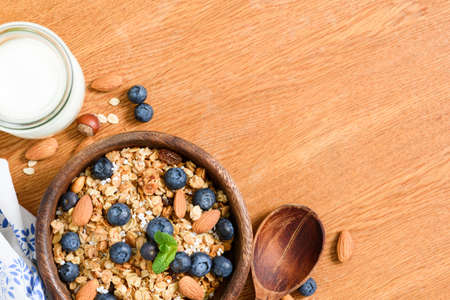 Granola with nuts and berries, milk on wooden table. Top view with copy space for text. Concept of weight loss diet, healthy lifestyle, healthy eating