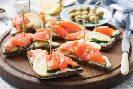 Canape sandwiches with salmon, cucumber and cream cheese. Closeup view Stock Photo