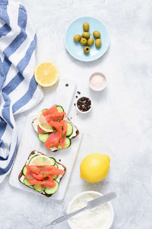 Sandwiches with salmon, cucumber and cream cheese on white background. Top view. Mediterranean cuisine
