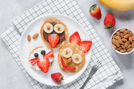 Funny pancakes with animal faces for kids on white plate. Top view Stock Photo