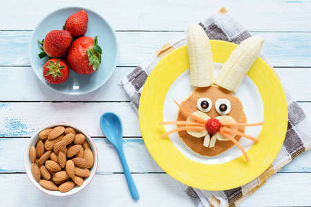 Healthy Easter Breakfast For Kids. Easter Bunny Shaped Pancake With Fruits. Top View 版權商用圖片