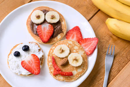 Pancakes With Funny Faces Decorated For Kids. Healthy Fruit Pancakes For Kids Meal