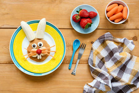 Easter breakfast for kids. Easter bunny shaped pancake with fruits on yellow plate. Colorful meal for children on wooden table, top view Stock Photo