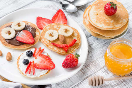 Colorful and funny breakfast for kids. Animal shaped pancakes on white plate. Creative food art, healthy breakfast for children concept Stock Photo