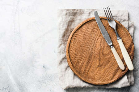 Vintage silverware and wooden board on grey concrete background. Top view, copy space for text Stock Photo