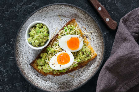 Toast with egg and avocado guacamole top view. Healthy snack, healthy eating concept Stock Photo