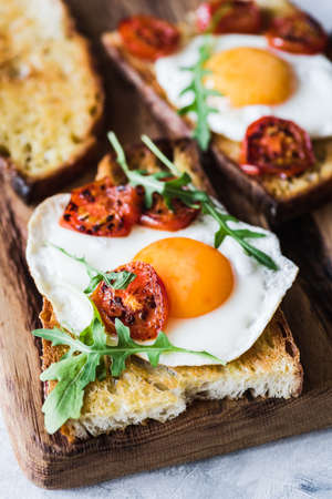 Breakfast toast with egg, roasted tomatoes and arugula salad. Closeup view