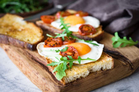 Healthy breakfast toast with egg, roasted tomato and arugula on rustic wooden cutting board. Closeup view