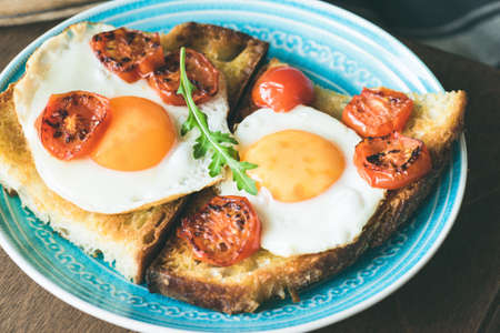 Breakfast toast with egg, roasted tomatoes and arugula salad on blue plate. Closeup view