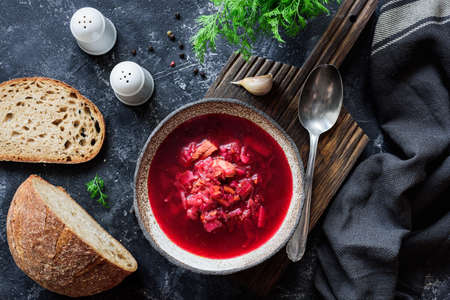 Ukrainian Borscht soup served with fresh dill, bread and garlic on dark background. Traditional cuisine