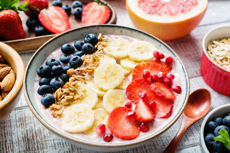 Acai smoothie bowl with banana, strawberry, blueberry and granola. Concept of healthy lifestyle, dieting, weight loss Stock Photo