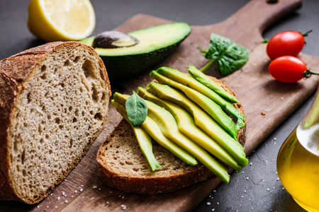 Avocado and rye bread toast on cutting board. Closeup view
