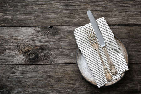 Vintage silverware cutlery and textile on rustic wooden background. Table setting with copy space for text. Top view