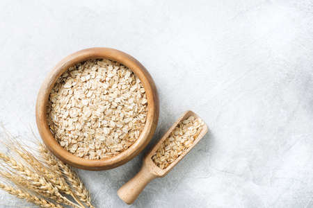 Rolled oats in wooden bowl on grey background with copy space for text. Concept of healthy eating, healthy lifestyle, dieting, weight loss Standard-Bild