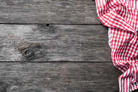 Red checkered textile on rustic wood. Food background with copy space for text. Picnic, menu, restaurant, home cooking concept