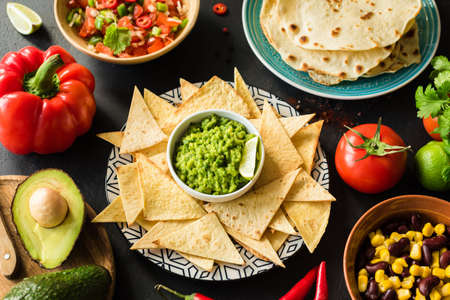 Mexican food Guacamole Nachos Tortilla chips salsa and beans on dark table. Food plate, Mexican cuisine