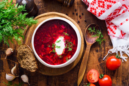 Borscht with sour cream - traditional Ukrainian and Russian beetroot soup. Rustic style. Table top view Stock Photo