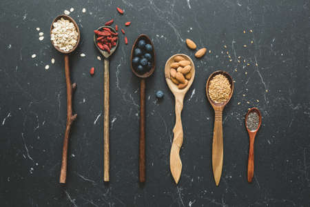 Superfood selection in wooden spoons on dark marble background. Top view