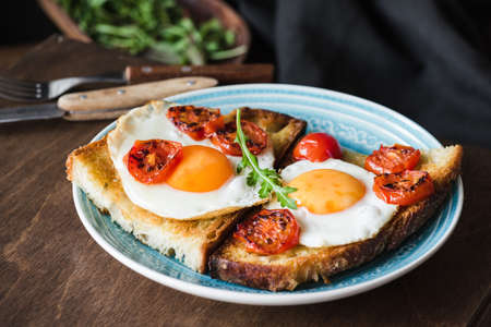 Breakfast toast with egg, arugula and roasted tomato, closeup view. Horizontal composition. Healthy eating, healthy lifestyle concept Stock Photo