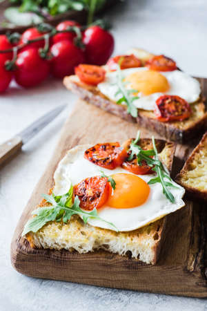 Breakfast toast with egg, arugula and roasted tomato, closeup view. Vertical Stock Photo