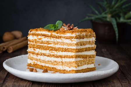 Slice of layered honey cake. Russian cake Medovik with walnuts. Horizontal, closeup view Stock Photo