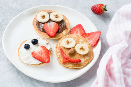 Pancakes art for kids on white plate. Colorful kids meal. Healthy breakfast concept