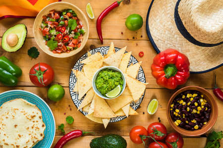 Traditional Mexican food on wooden table. Tortilla chips, guacamole, nachos, beans and salsa. Table top view
