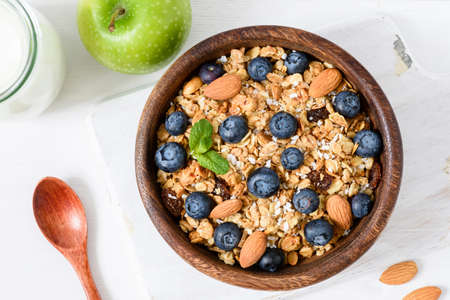 Granola bowl with blueberries and almond nuts on white table. Healthy breakfast, dieting, vegan, vegetarian, weight loss concept Stock Photo