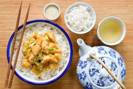 Chinese orange chicken with rice, china teapot and cup of green tea on bamboo background. Top view. Traditional chinese cuisine