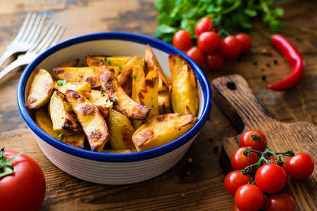 Roasted spicy potato wedges with paprika in bowl on wooden table. Homemade appetizer or side dish for dinner