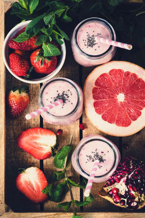 Pink fresh smoothies with grapefruit, strawberry and pomegranate in wooden tray, top view, selective focus, toned image. Healthy lifestyle, detox, dieting, clean eating, vegan, vegetarian concept
