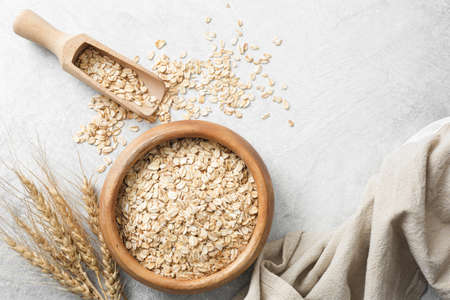 Rolled oats or oat flakes in wooden bowl on concrete background, top view. Healthy eating, healthy lifestyle, gluten free, vegan, dieting, vegetarian concept
