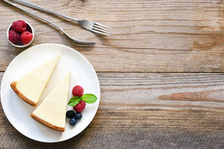New York cheesecake or classic cheesecake with fresh berries on white plate, wooden table background and copy space for text Standard-Bild