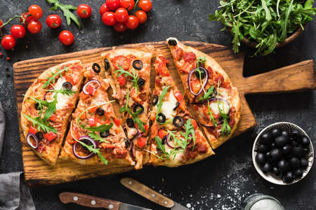 Flatbread pizza garnished with fresh arugula on wooden pizza board, top view. Dark stone background