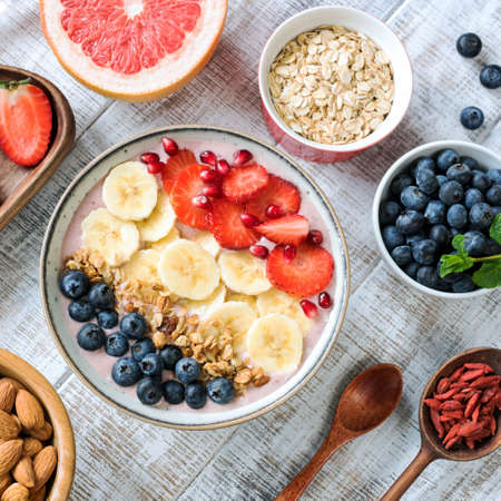 Acai smoothie bowl with banana, strawberries, blueberries and granola, top view, square crop. Healthy eating, healthy lifestyle, dieting, fitness concept