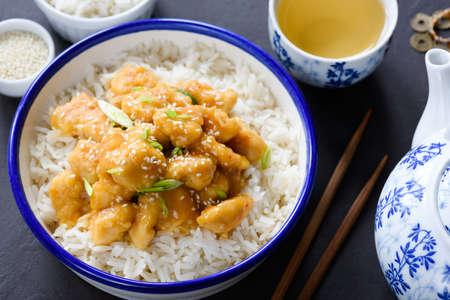 Teriyaki chicken with rice and green tea in china tea pot. Closeup view. Asian cuisine