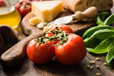Tomatoes on vine, olive oil and parmesan cheese. Italian food background or still life