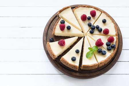 Cheesecake with summer berries cut into pieces on white background. Top view with copy space for text Foto de archivo