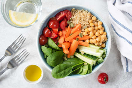 Top view of Salad bowl with quinoa, chickpeas, cucumber, baby carrots, spinach and tomatoes. Concept of healthy eating, healthy lifestyle, detox diet, vegan and vegetarian food Фото со стока