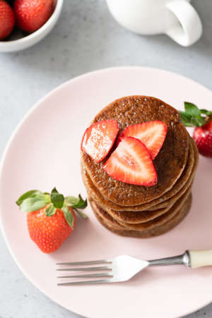 Gluten free buckwheat pancakes with strawberries on pink plate. Top view, selective focus. Trendy vegan food