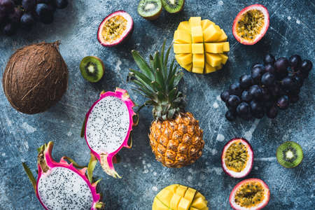 Tropical fruits on stone background, flat lay, table top view. Pitaya, passion fruit, grapes, kiwi, coconut, mango and pineapple