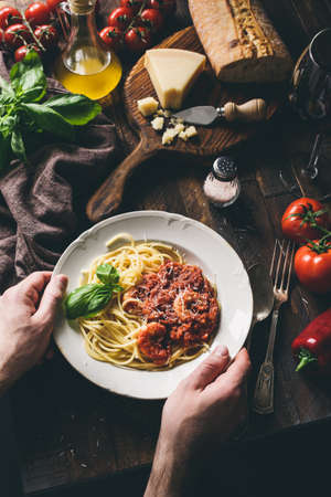 Spaghetti with tomato sauce and shrimps, italian cuisine. Hands holding plate of pasta with sauce. Rustic style. Top view, copy space for text