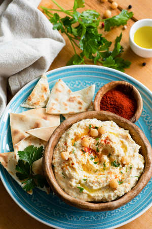 Homemade chickpea hummus, pita flatbread and smoked paprika. Traditional middle eastern food, meze or appetizer. Healthy vegan meal