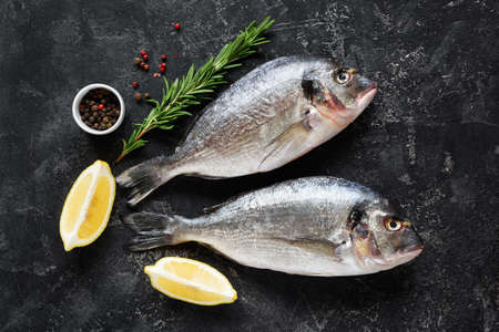 Fresh dorado or sea bass fish on slate background with cooking ingredients, lemon rosemary and spices. Top view Stock Photo