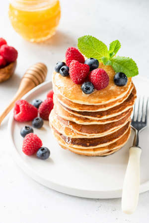 Pancakes with berries, honey and mint on white plate, closeup view, selective focus. Stack of pancakes. Tasty dessert or breakfast