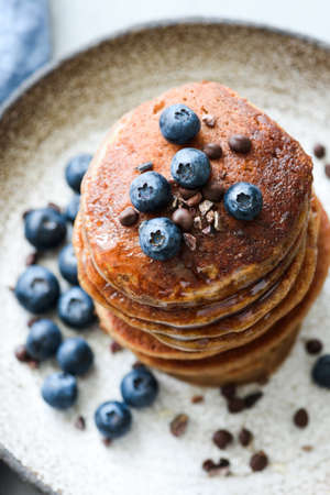 Buckwheat pancakes with cocoa nibs and blueberries. Closeup view, selective focus