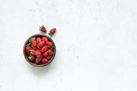 Strawberry in a bowl. Fresh strawberries. Harvest of fresh organic strawberries on white concrete background. Top view with copy space for text Stock Photo