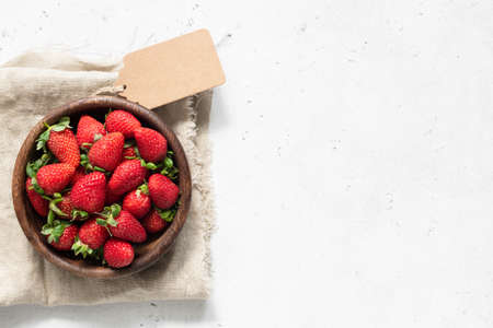 Strawberry in bowl. Fresh strawberries on white concrete background. Top view with copy space for text