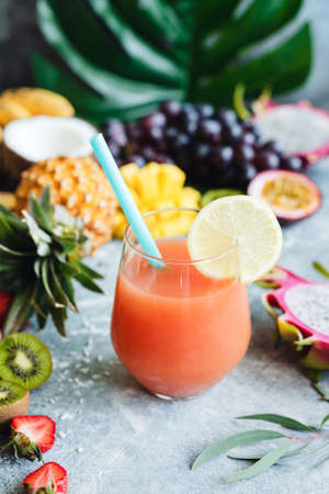 Tropical juice or cocktail in a glass with drinking straw. Closeup view, selective focus Stock Photo